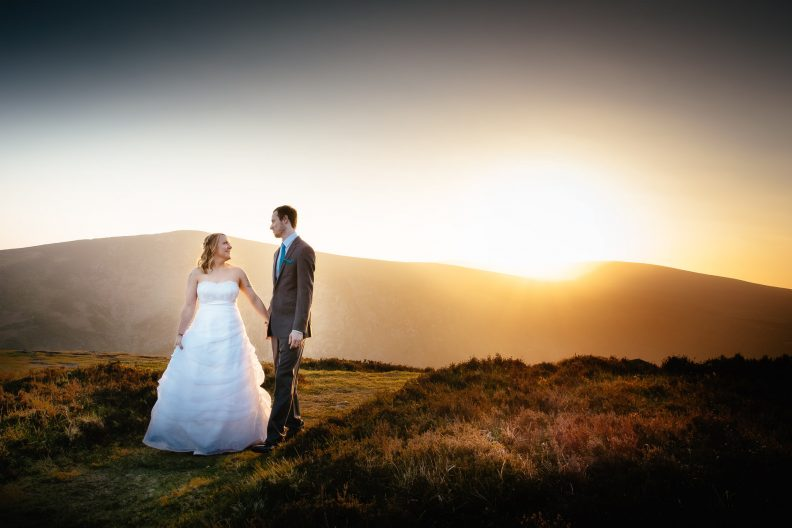 bride and groom walking through meadow at sunset in wicklow mountains