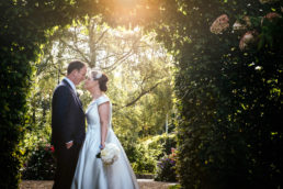 bride and groom under sun filtered arch