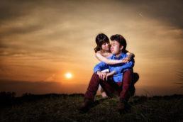 engaged couple embracing during sunset