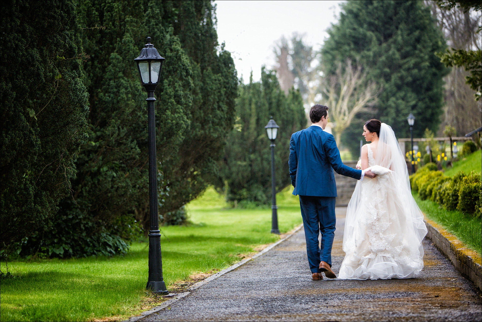 bride and groom walking through the grounds of Bellingham Castle