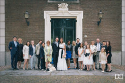 wedding party with a dog posing for a photo outside a church at an Amsterdam wedding