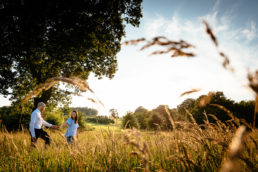 engaged couple walking through meadow at sunset