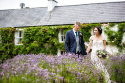 bride and groom walking through lavender plants at Glebe House Dowth