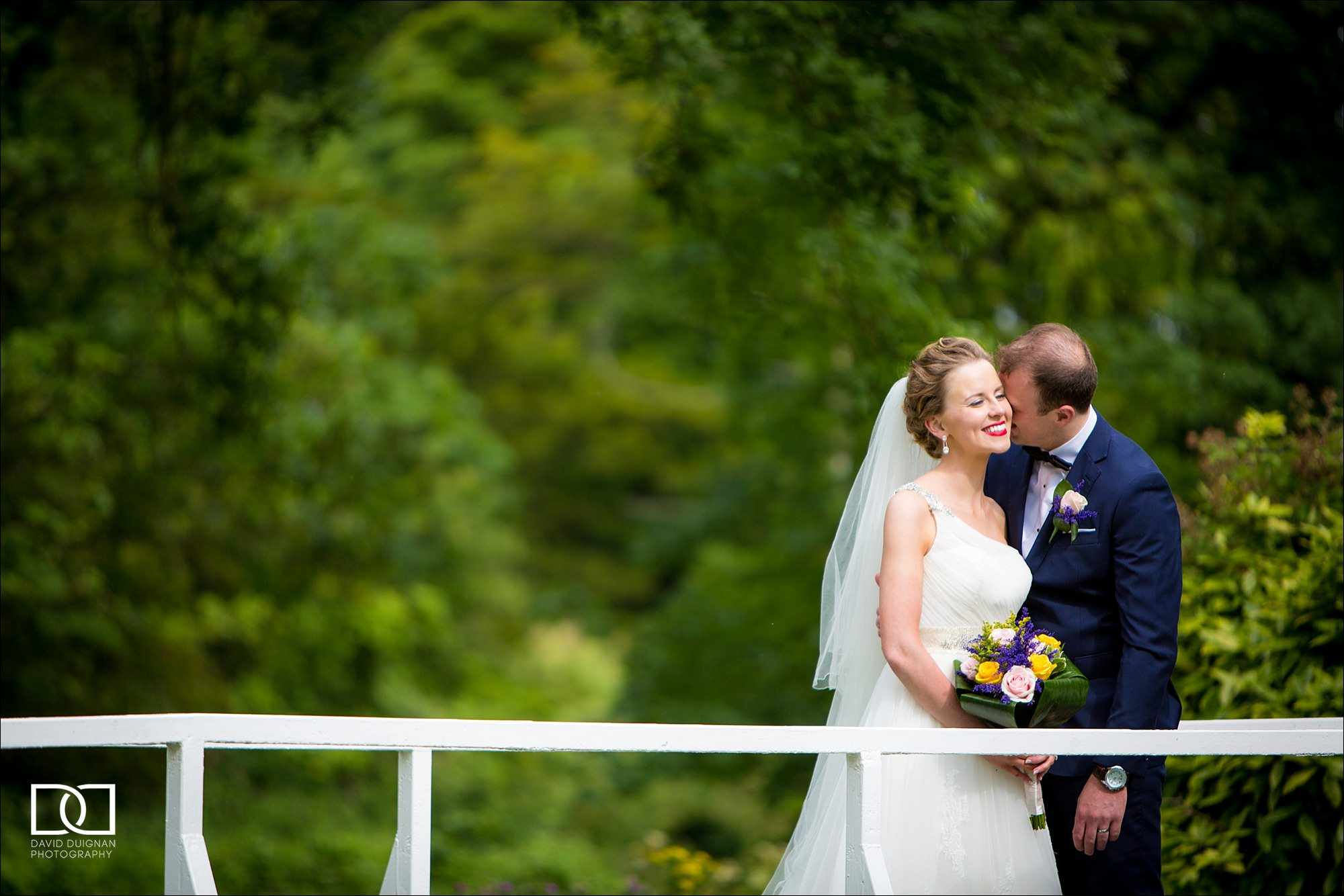 bride and groom on a bridge at their Bellingham Castle Wedding