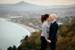 engaged couple looking out over killiney hill