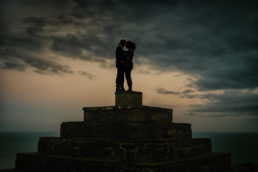 engaged couple looking out over dublin at dusk