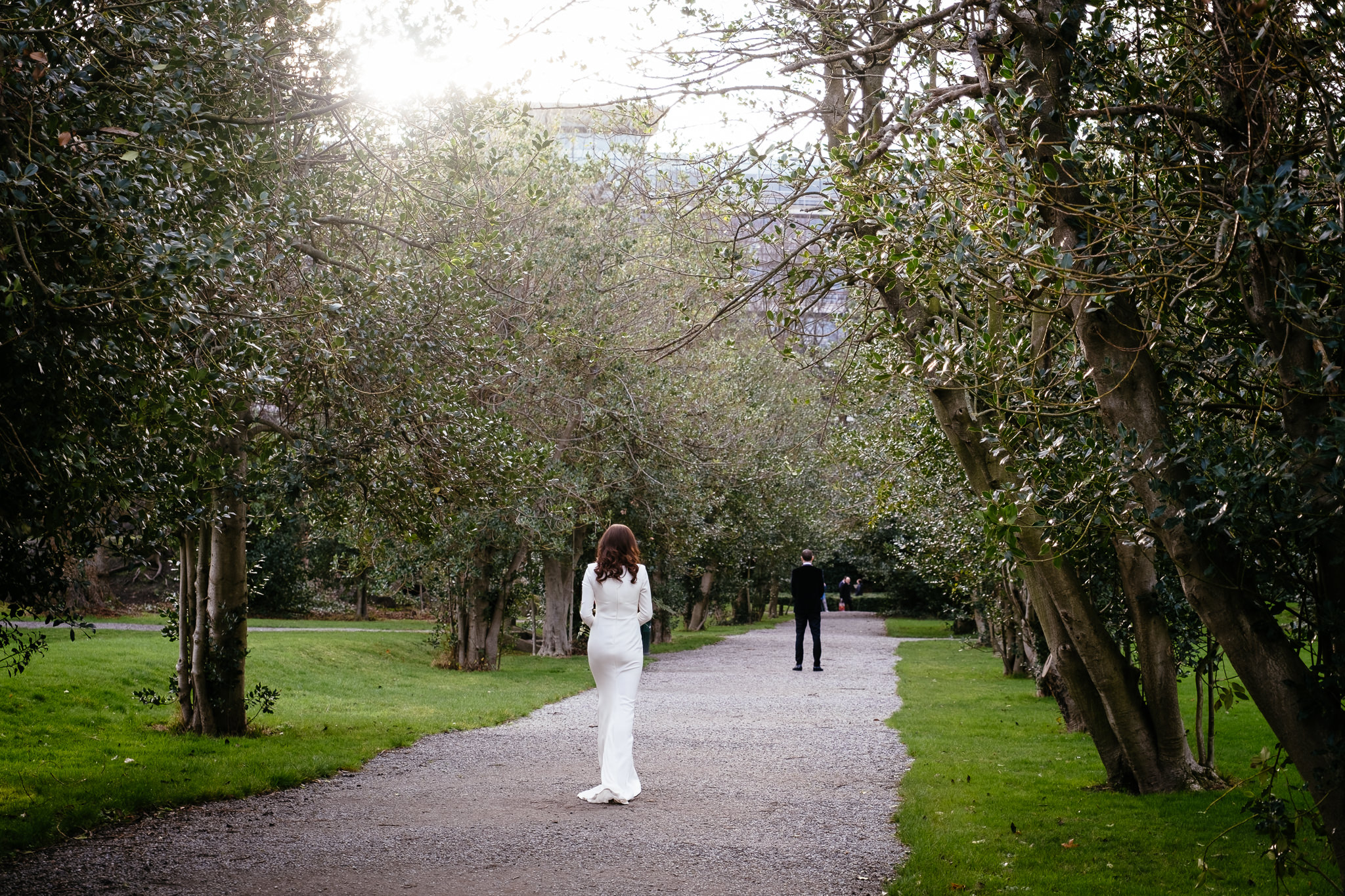 bride walking up behind groom before their first look in a dublin park