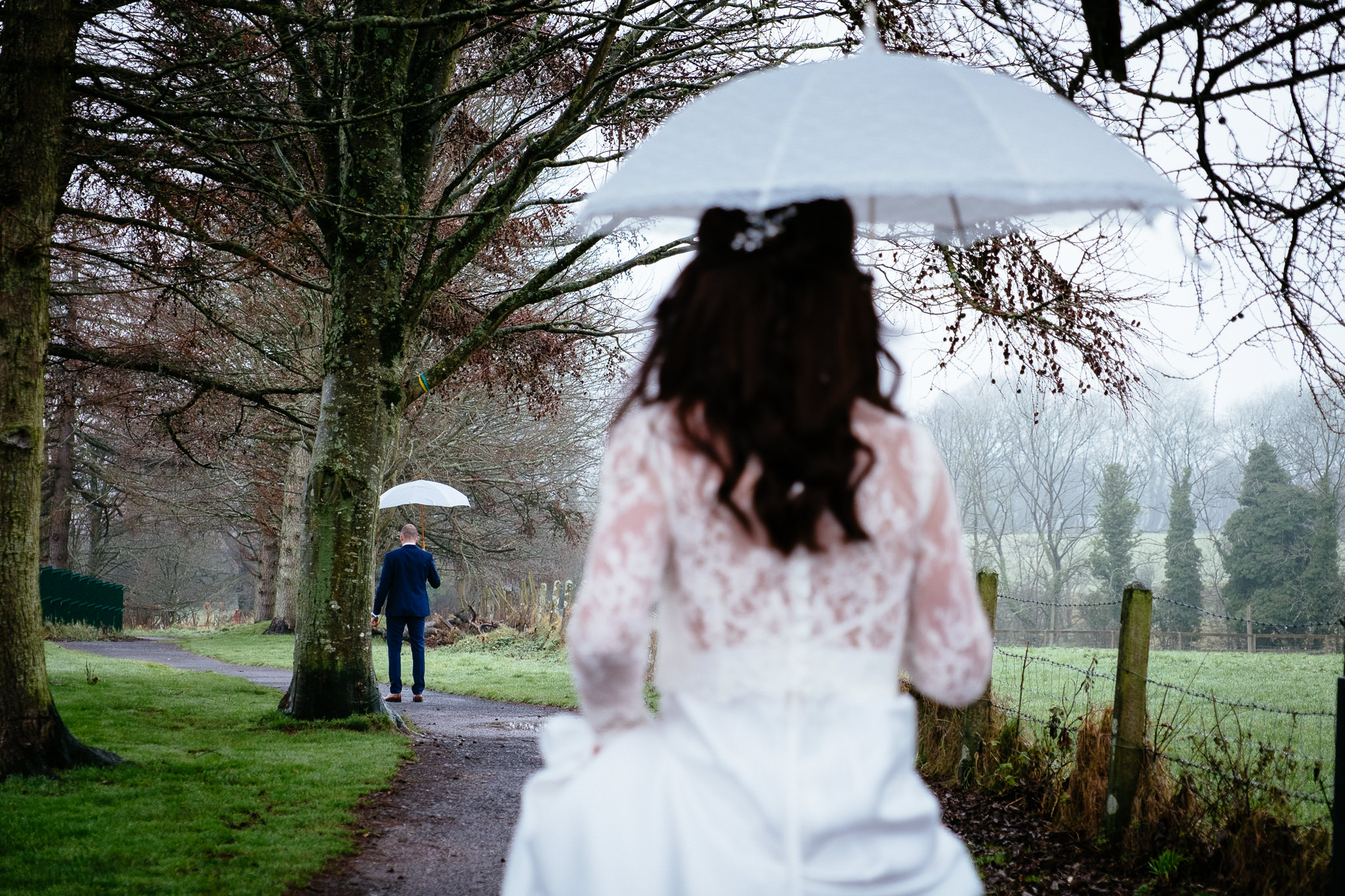 irst look between a bride and groom in the rain