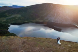 wedding couple overlooking lough tay at sunset in dublin mountains