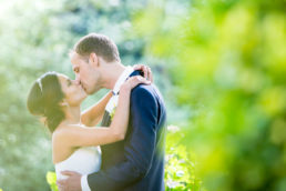 bride and groom kissing filtered sunlight