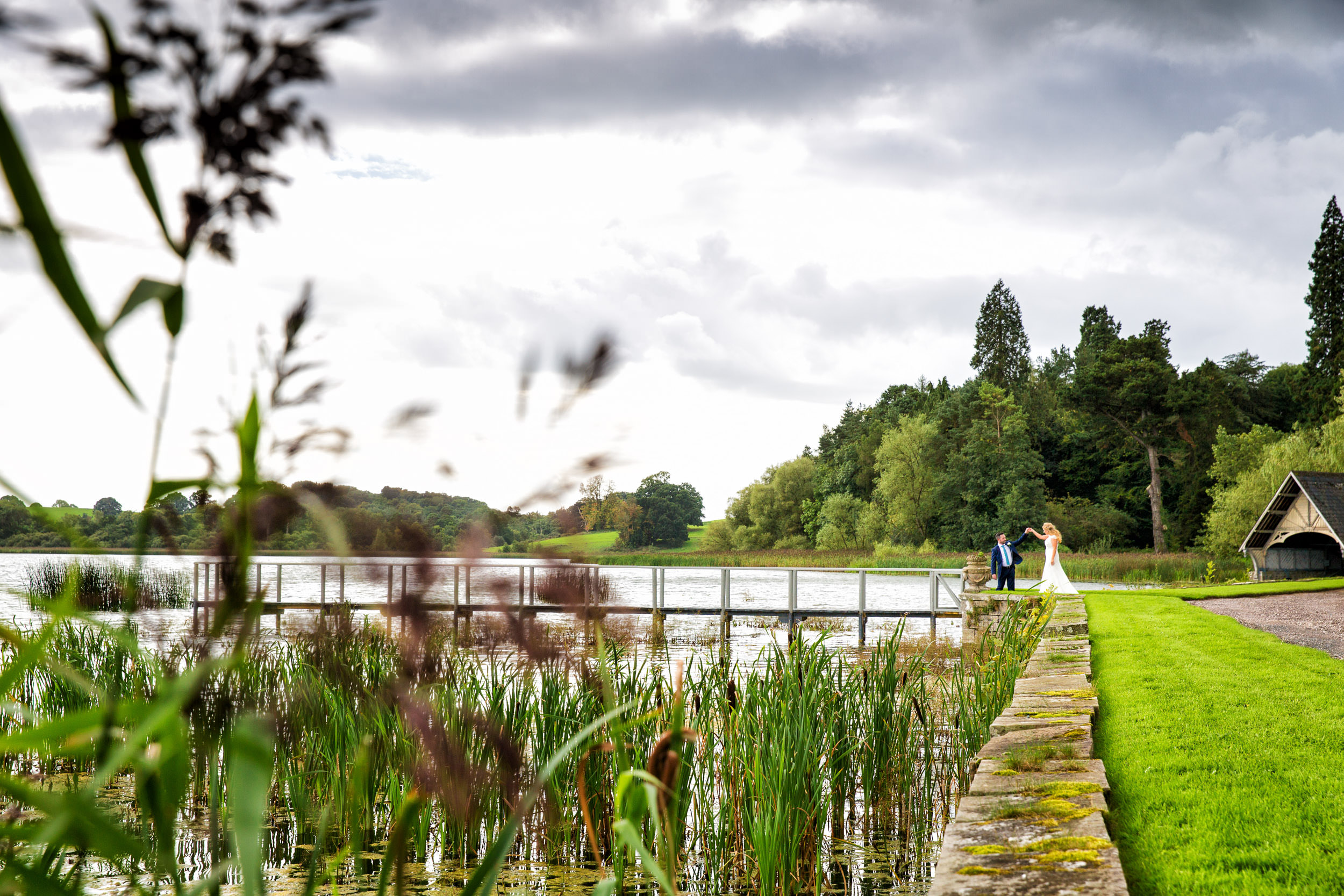 bride and groom walking alomng the jetty in Castle Leslie with the boathouse in the background during their wedding reception