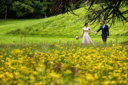 bride and groom walking in a field of yellow flowers in belleek castle mayo ireland