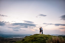 engaged couple kissing at sunset on a mountain in donegal
