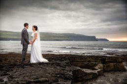 Bride and groom embracing on beach in west of ireland