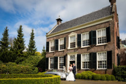 bride and groom embracing outside dutch house