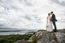bride and groom embracing on a rock in kerry ireland