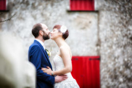 bride and groom kissing in front of old house
