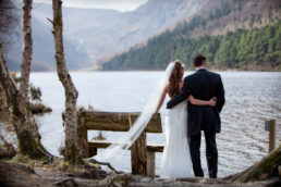 bride and groom looking out onto a lake at glendalough