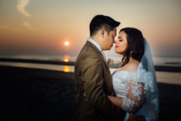 bride and groom embracing on a beach at sunset