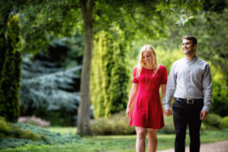 engaged couple walking hand in hand through Merrion Park in Dublin city