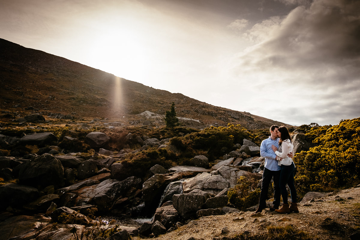engaged couple on Irish mountain with sun setting behind them