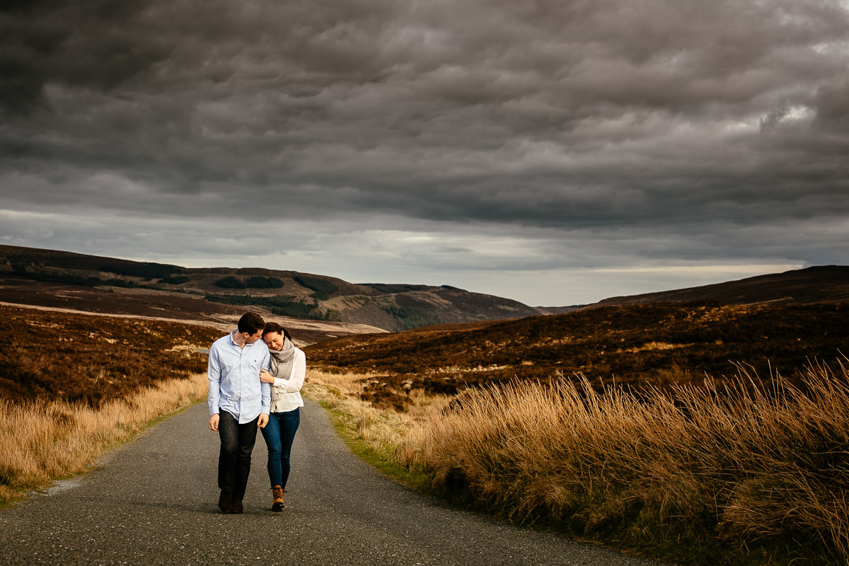 engaged couple walking along deserted Irish country road