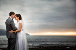 bride and groom embracing at sunset with sea and cliffs in background at their wedding at hotel doolin