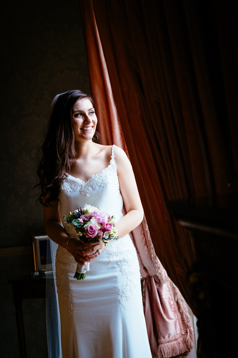 bride at window holding bouquet at her outdoor wedding at Tankardstown House Slane