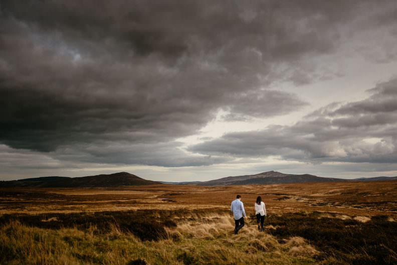 engaged couple walking holding hands in wicklow mountains