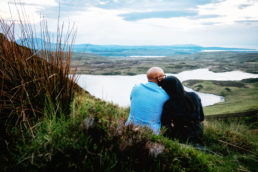 engaged couple sitting on mountain overlooking a lake in donegal ireland