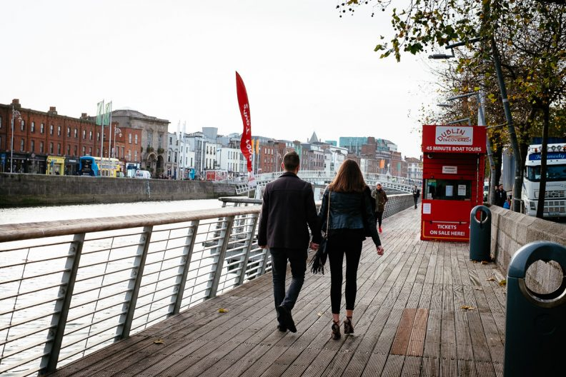 couple walking along the river liffey boardwalk in dublin