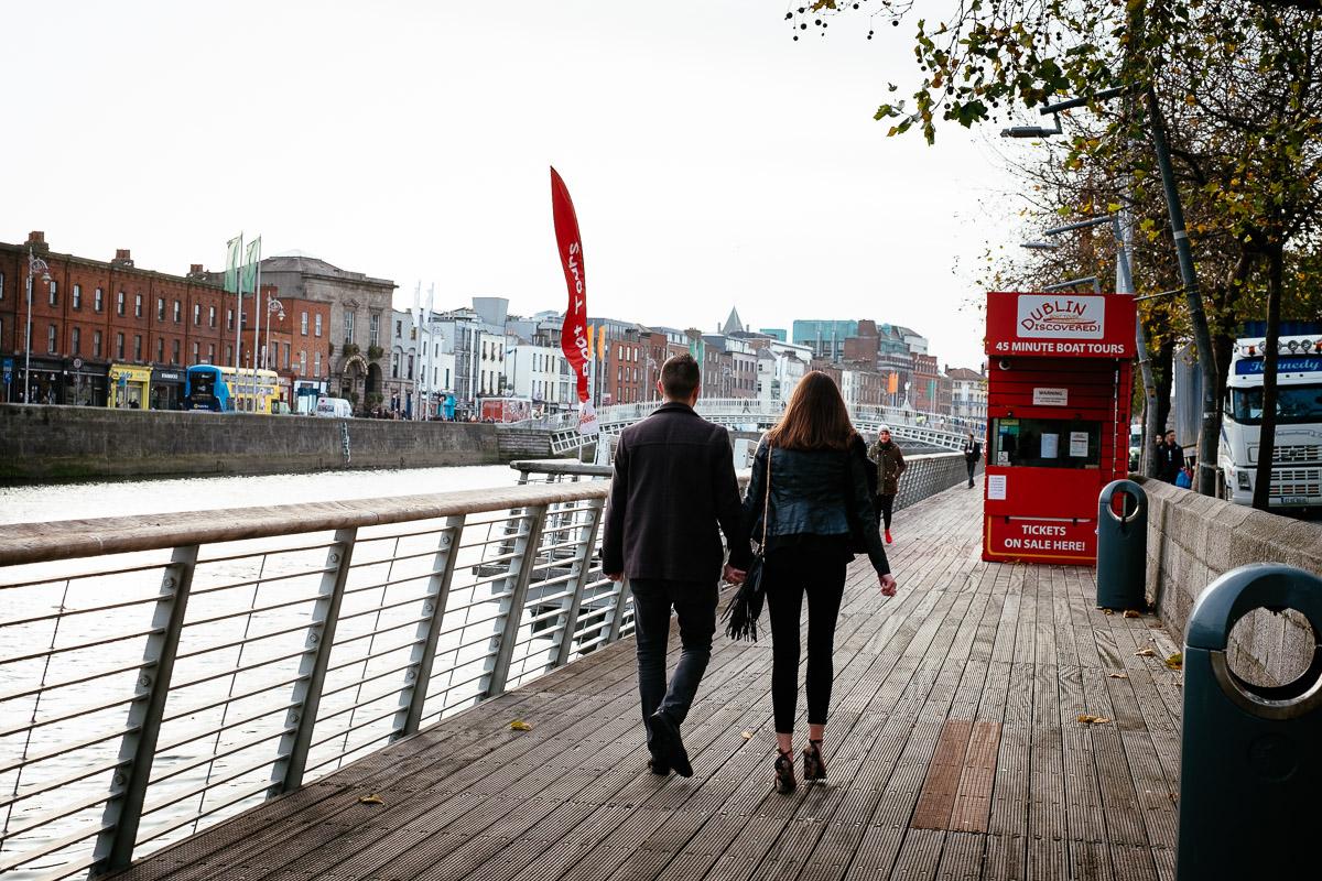 couple walking along the river liffey boardwalk in dublin