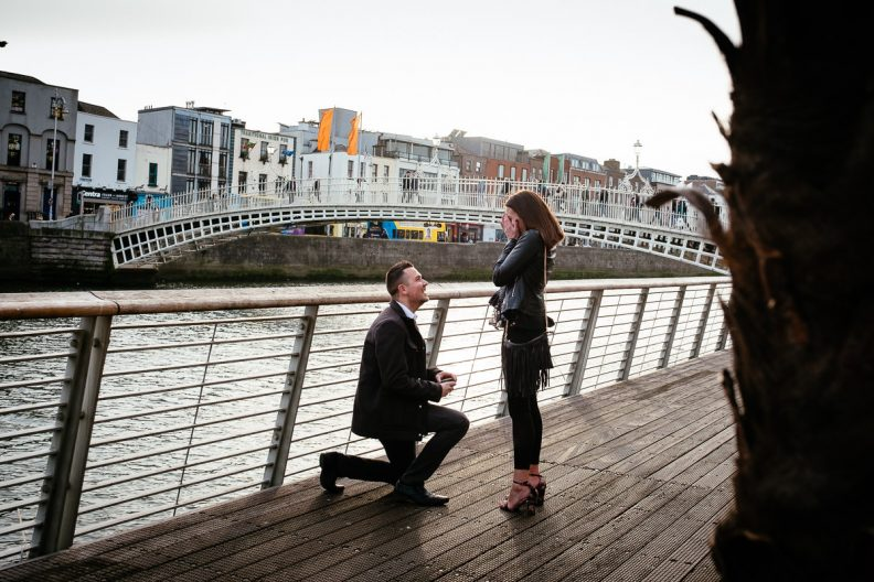 guy proposing to his girlfriend by the river liffey boardwalk in dublin