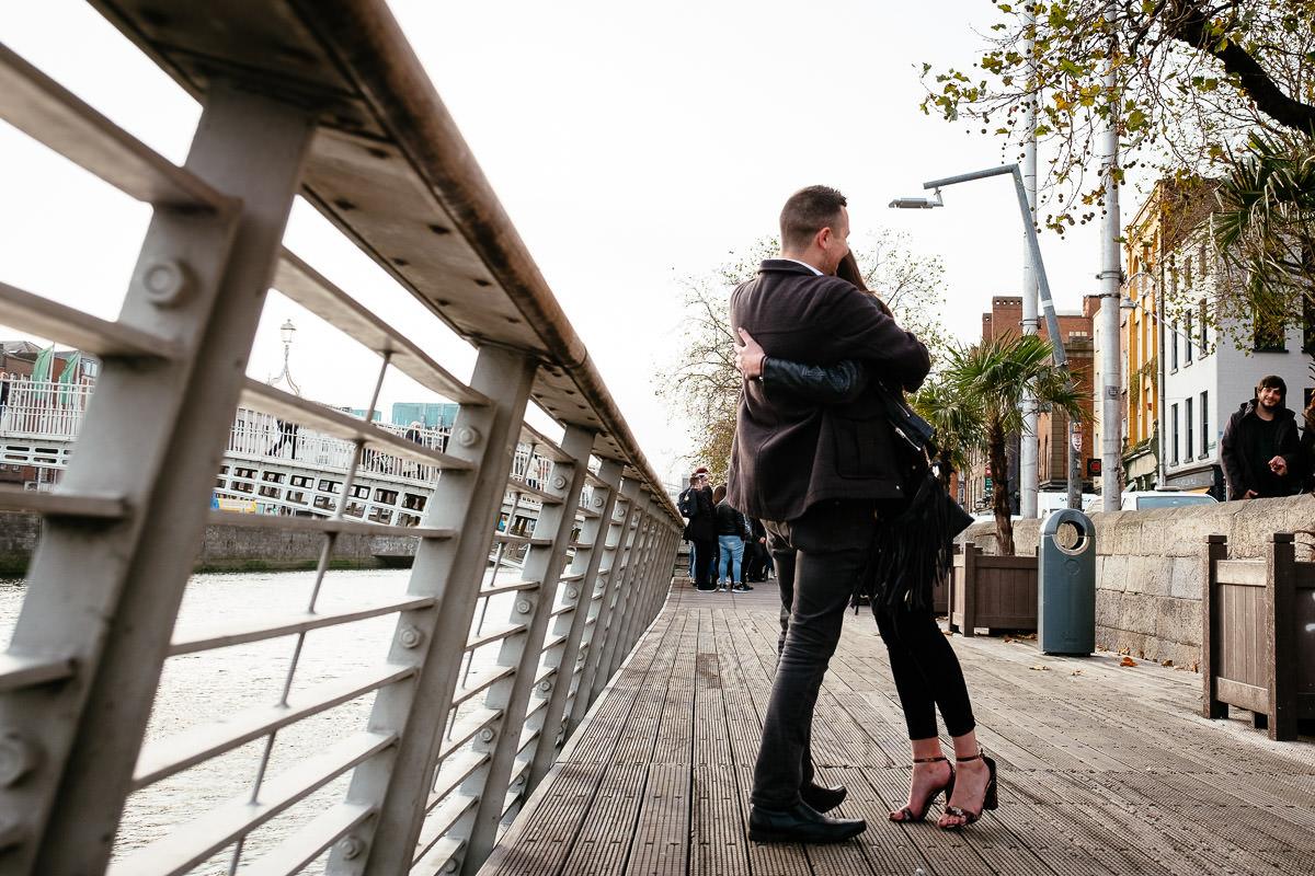 guy proposing to his girlfriend by the river liffey boardwalk in dublin