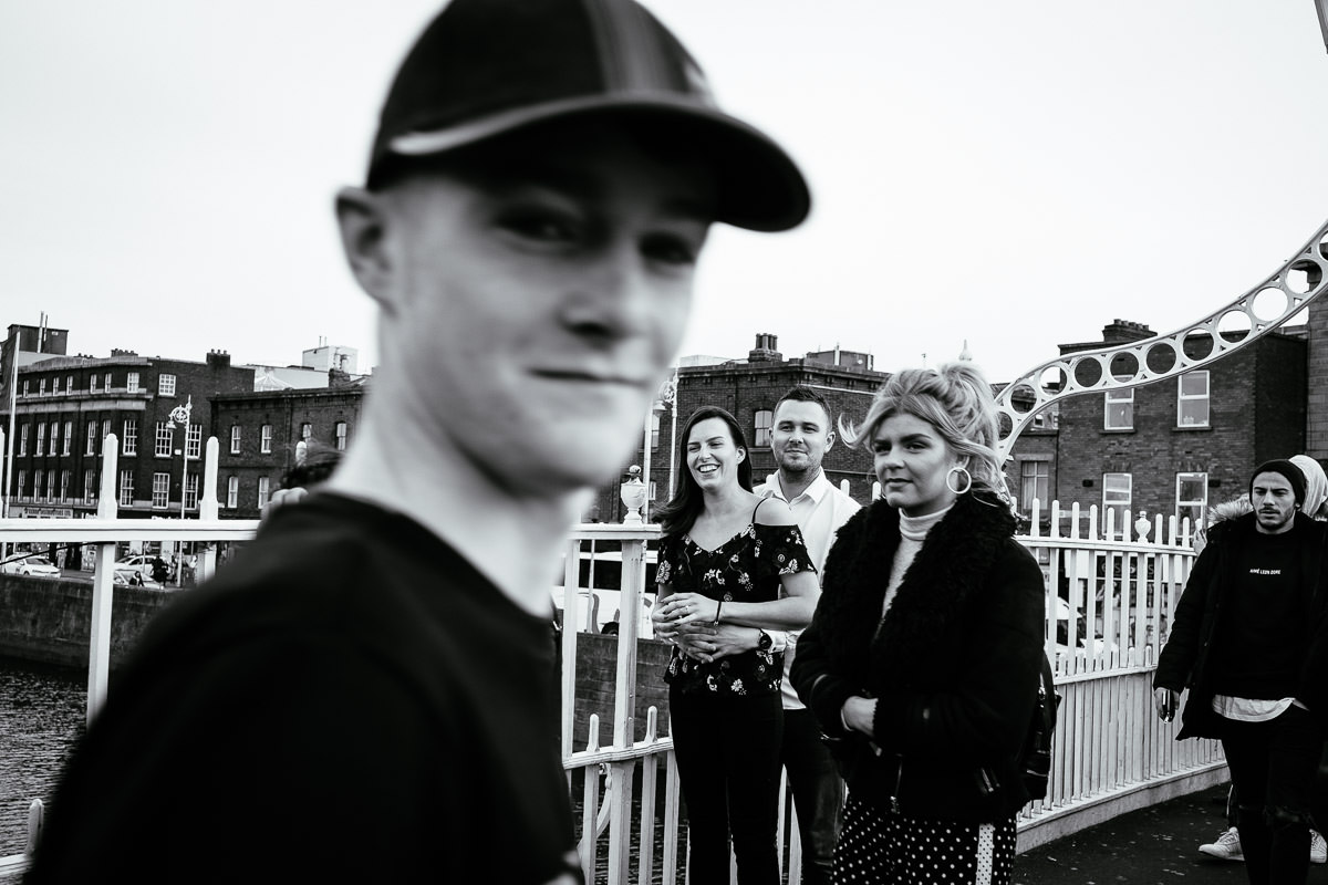 newly engaged couple with a pedestrian on the ha'penny bridge in dublin