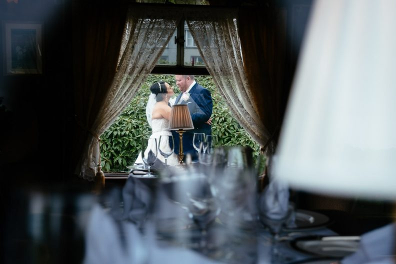 bride and groom kissing through train carriage at glenlo abbey hotel wedding