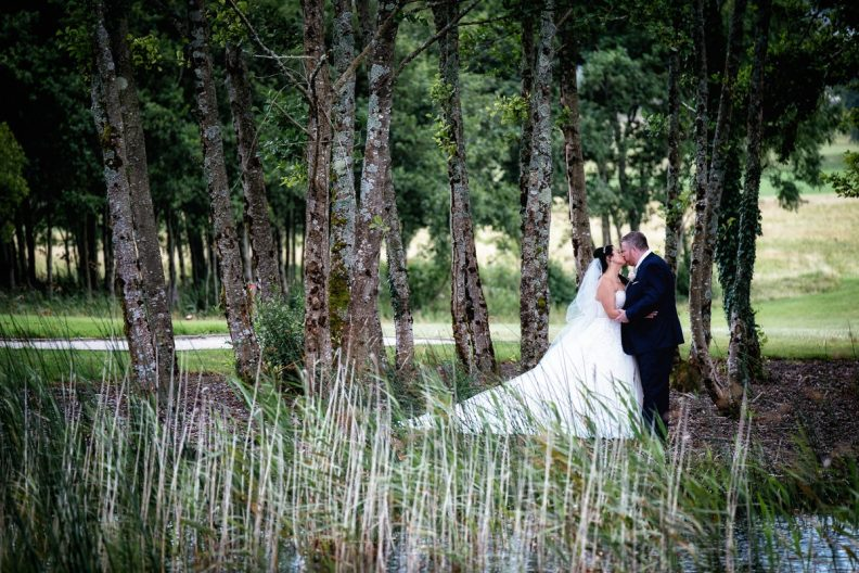 bride and groom kissing in the woods at glenlo abbey hotel wedding