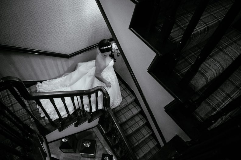 bride walking down stairs at gleno abbey hotel wedding