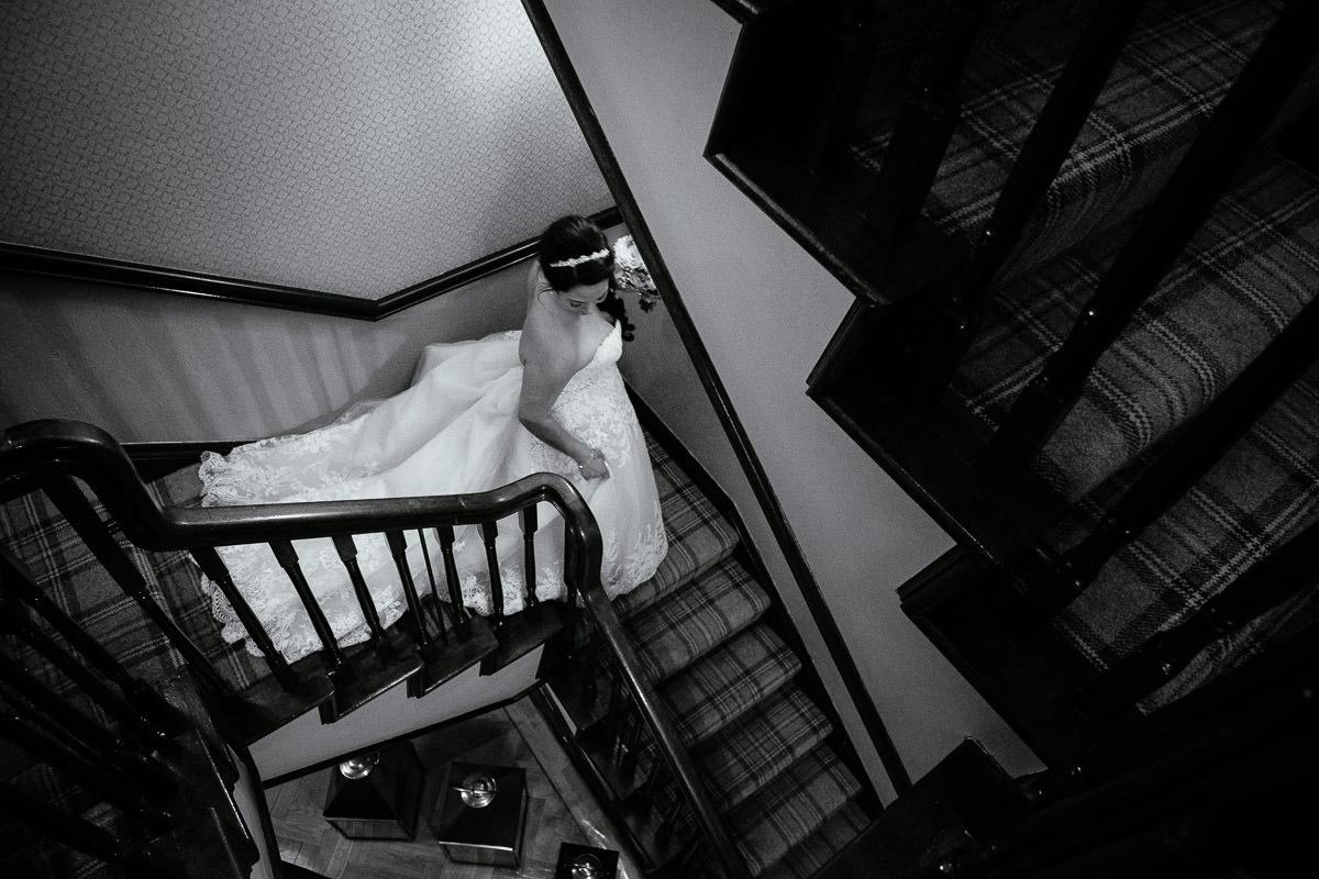 bride walking down stairs at gleno abbey hotel wedding
