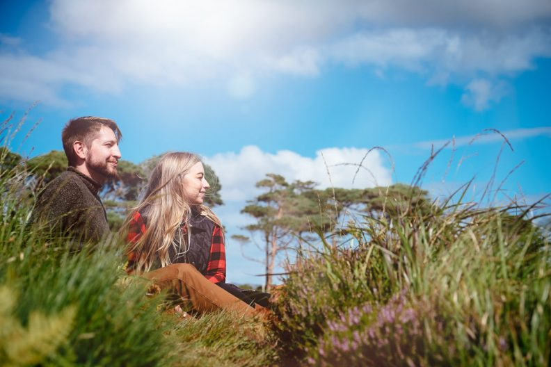 engaged couple looking away in wild atlantic way ireland