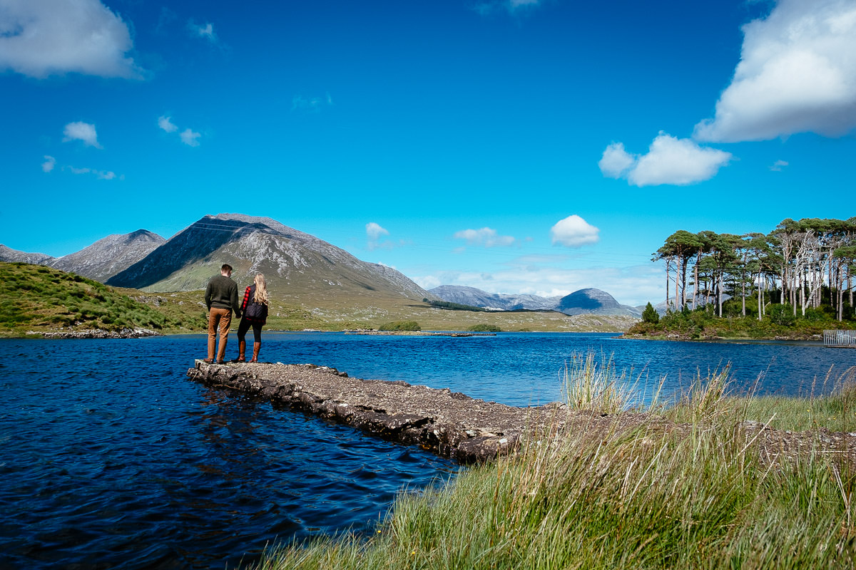 engaged couple standing by a lake in wild atlantic way ireland