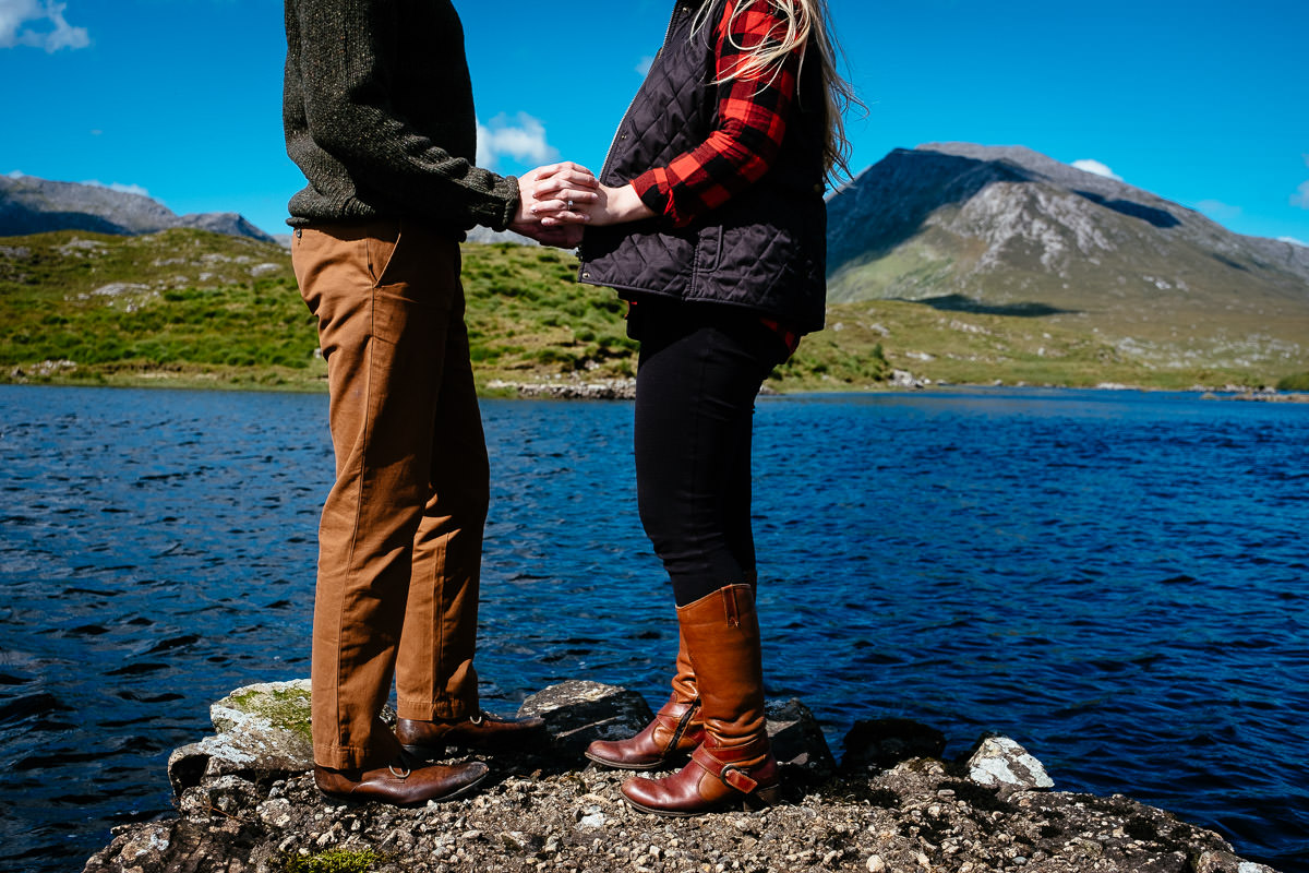 engaged couple holding hands by a lake in wild atlantic way ireland