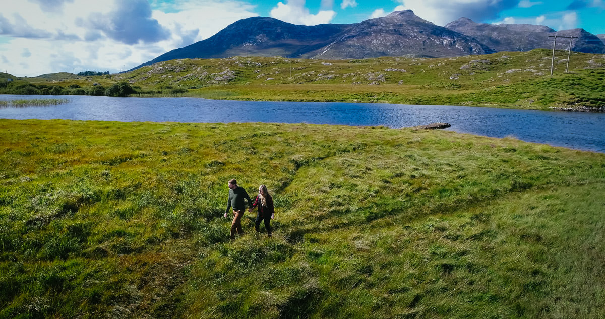 engaged couple walking by a lake in wild atlantic way ireland