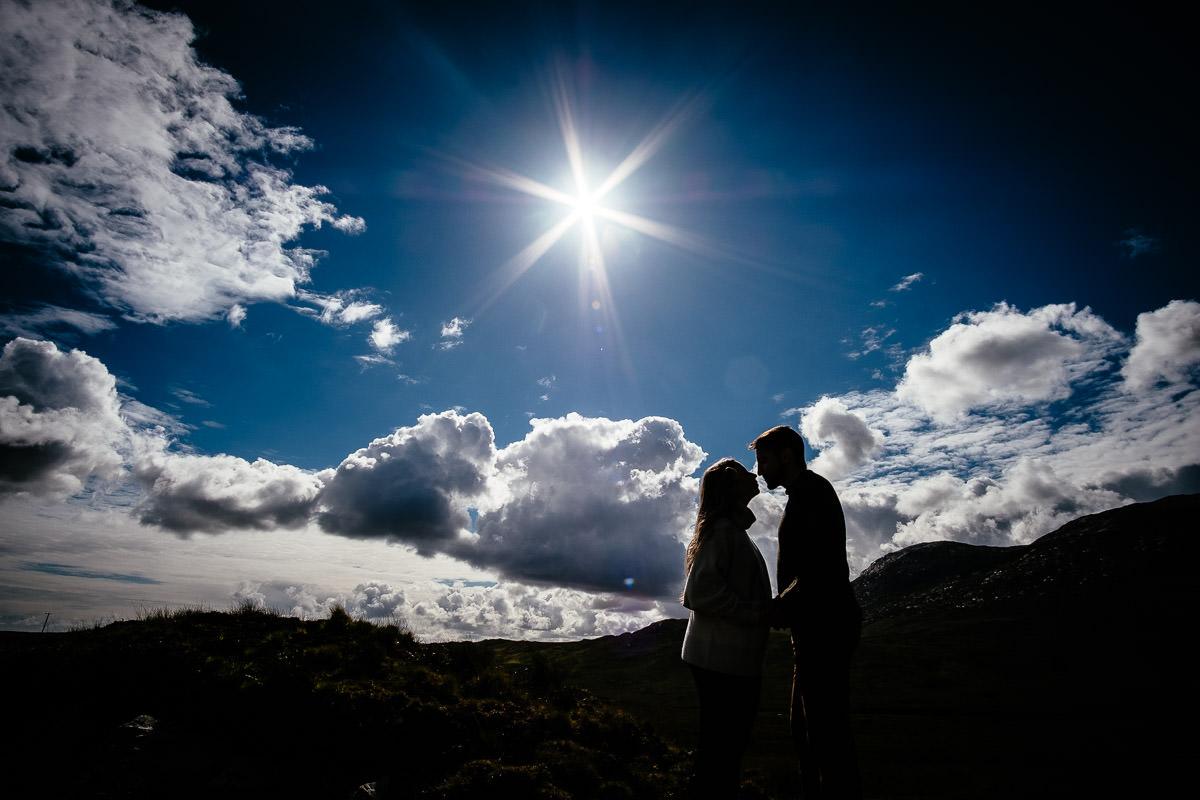 engaged couple walking through mountains in wild atlantic way ireland