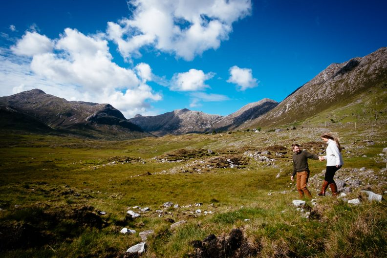 engaged couple walking through mountains in wild atlantic way ireland