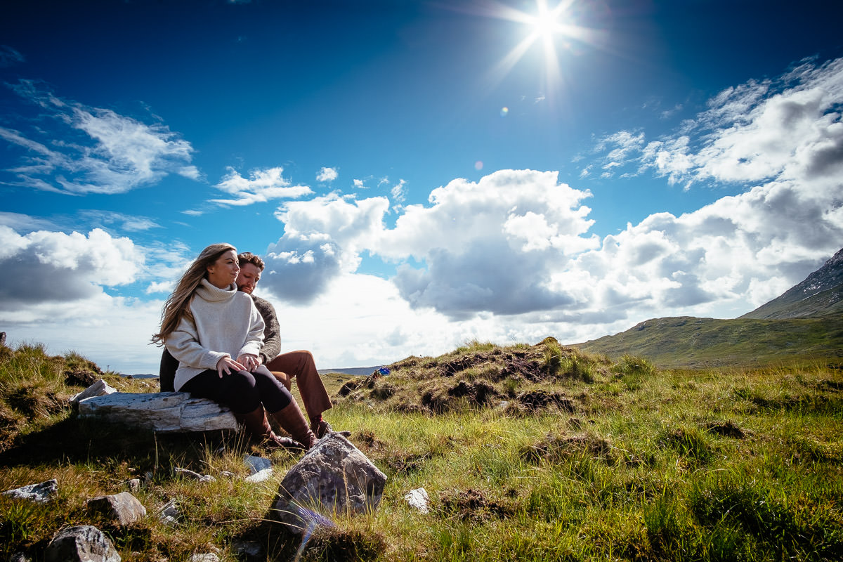engaged couple sitting in a mountain in wild atlantic way ireland
