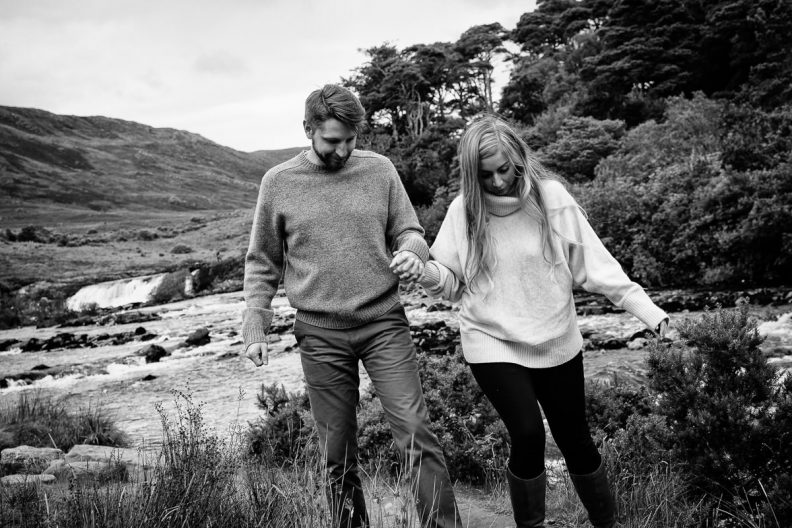 engaged couple walking by river in wild atlantic way ireland