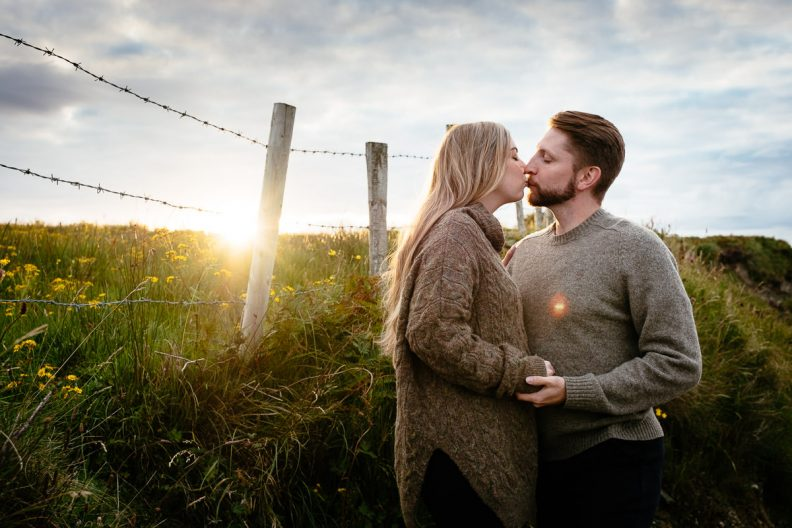 engaged couple kissing at sunset in wild atlantic way ireland