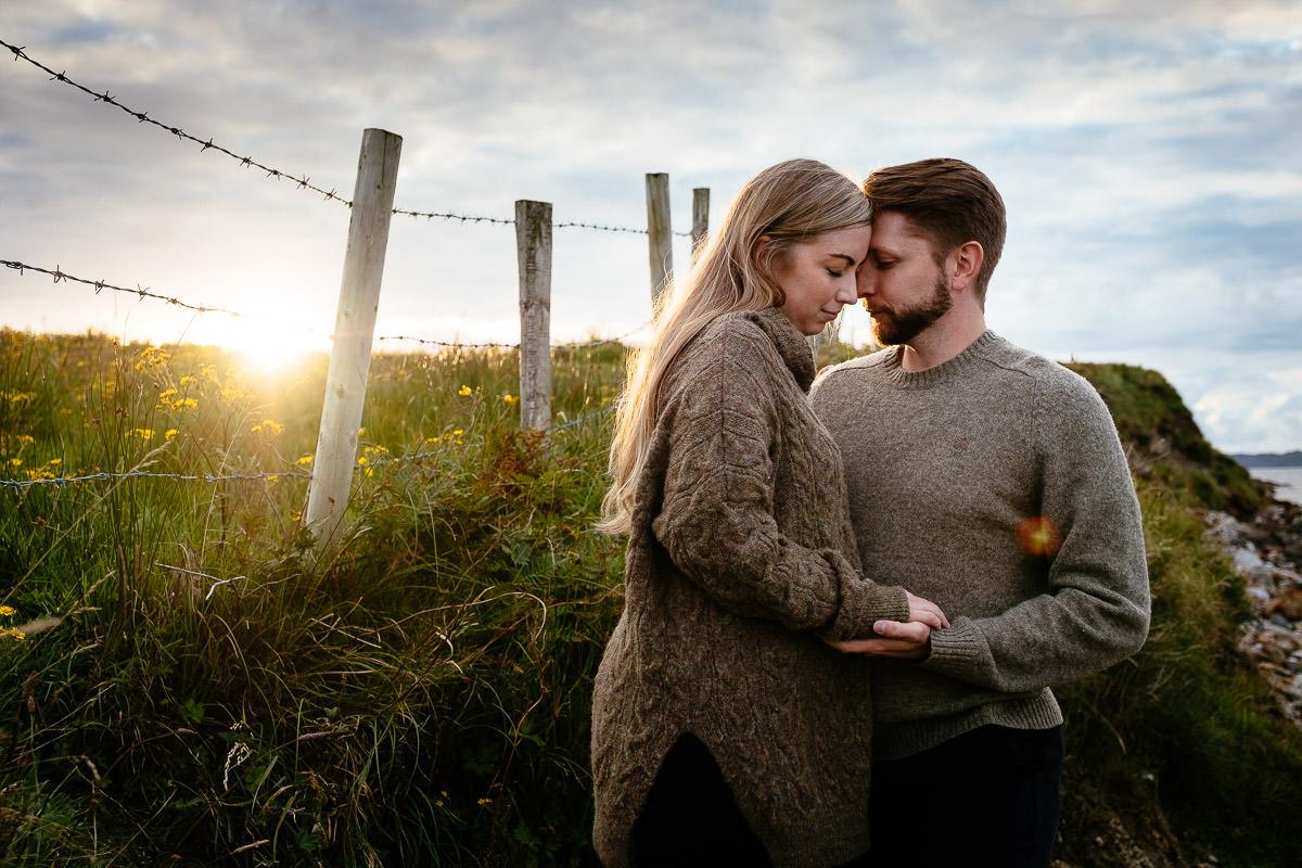 engaged couple kissing at sunset in wild atlantic way ireland