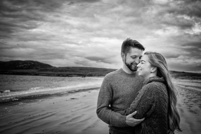 engaged couple hugging on a beach in wild atlantic way ireland